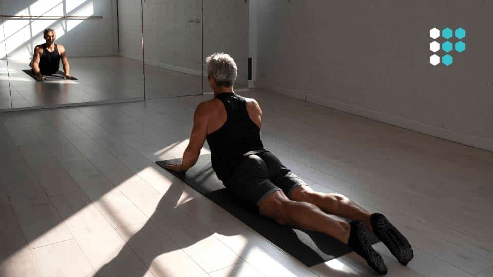 Man in black gym clothes doing yoga in front of a mirror