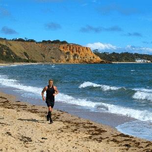 Man Running Along Beach In Black Sports Gear
