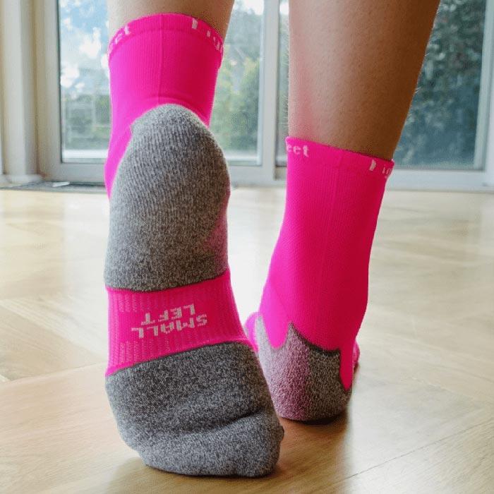 Women's feet wearing pink Lightfeet socks